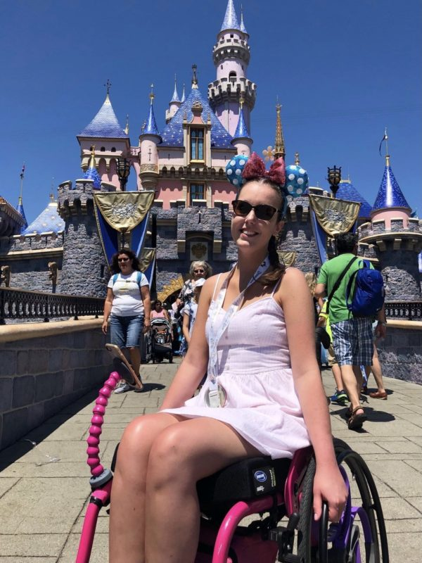 Lauren is wearing a pale pink dress whilst sitting in a pink wheelchair in front of the castle at Disneyland in Anaheim.