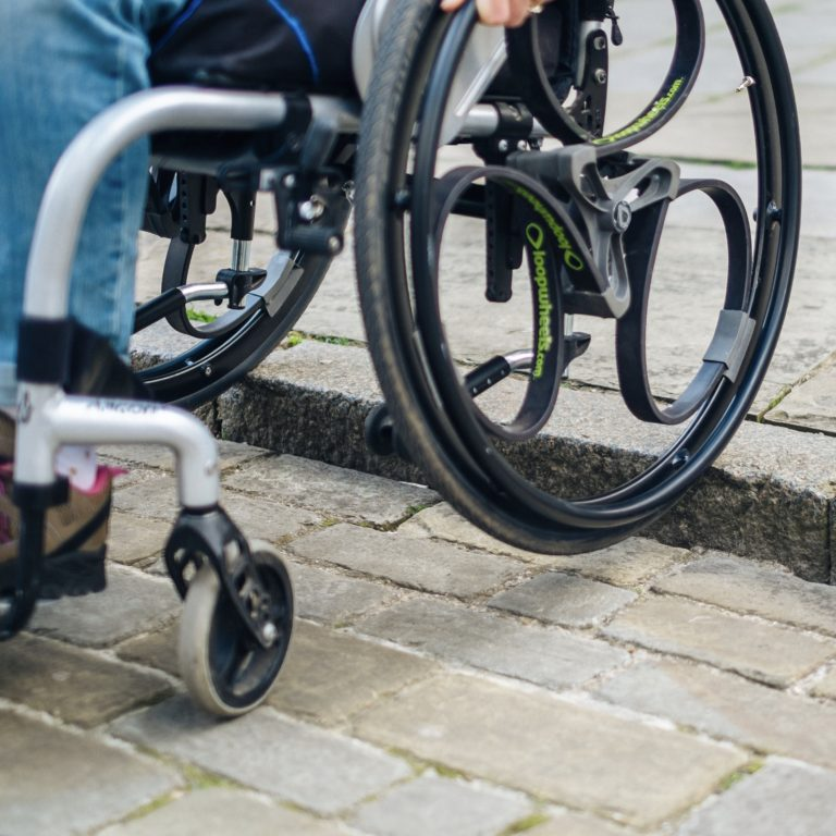 Black Loopwheels attached to a silver manual wheelchair. You can only see the users hand on one of the black push rims, as the wheels roll down a kerb.