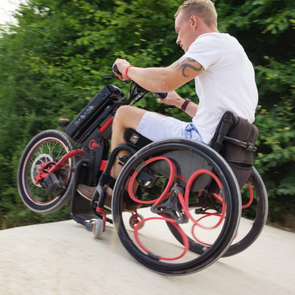 Red Loopwheels attached to a black manual wheelchair with a red powered trike attachment. The user is driving his wheelchair up a steep BMX ramp.