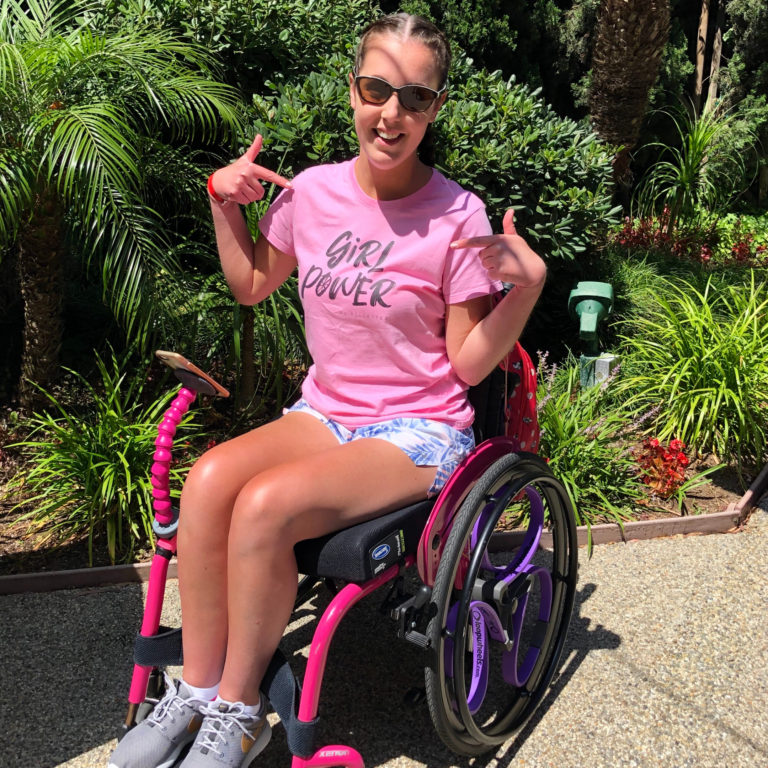 "Lauren is sitting in a bright pink wheelchair with purple Loopwheels, whilst pointing at her pink ""Girl Power"" t-shirt and smiling directly at the camera."