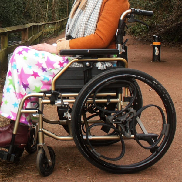 Black Loopwheels attached to a stationary gold manual wheelchair. You can only see the users legs which are wrapped in a multicoloured blanket.
