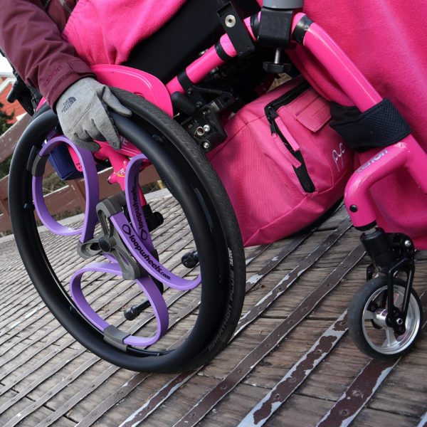 Purple Loopwheels attached to a pink manual wheelchair. You can only see the users hand on one of the black push rims, as the wheels glide over an uneven bridge.