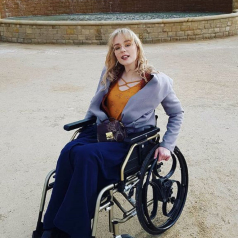 Lori is sitting in a gold wheelchair with black Loopwheels, whilst using a navy blanket to keep warm and smiling directly at the camera.