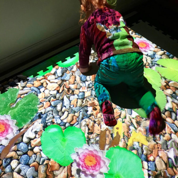 A young child using an interactive sensory floor projection called SENse.