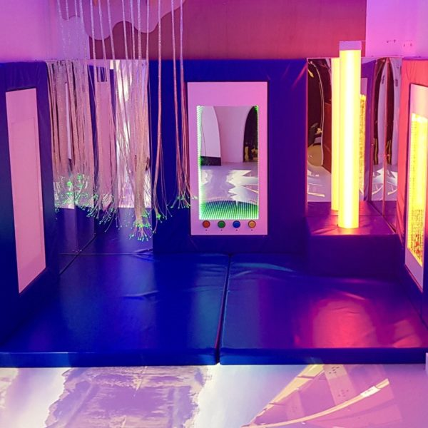 An immersive room with sensory lights, interactive screens and colourful soft padded walls and floors.