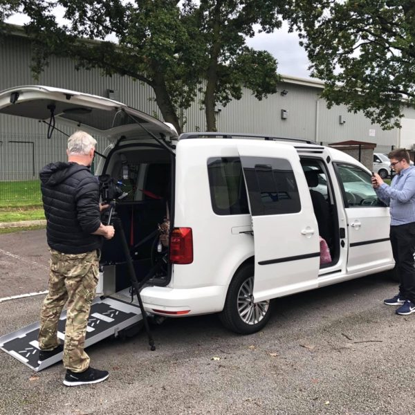 White Volkswagen Caddy Maxi with deployed wheelchair access ramp and opened sliding door. A cameraman is to the left-hand side filming the various features.
