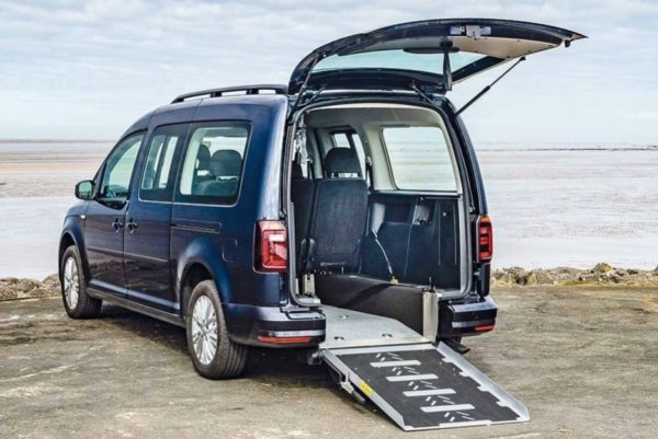 Navy Volkswagen Caddy Maxi with deployed wheelchair access ramp parked on the seafront.