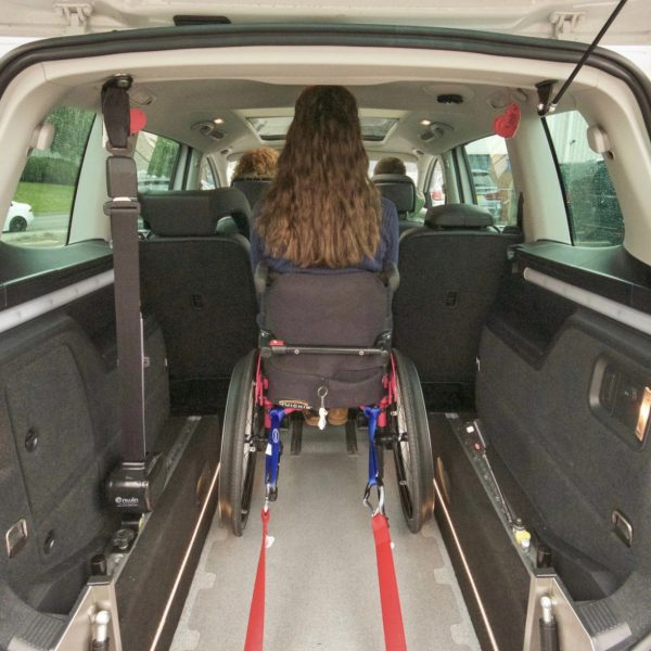 Lauren is sitting in a bright pink wheelchair that is strapped into a white Seat Alhambra using red tie down features.