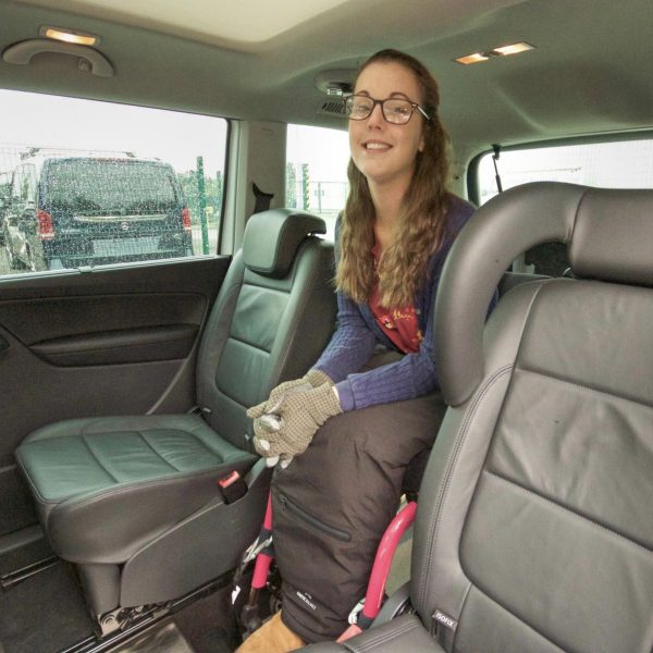 Lauren is sitting a white Seat Alhambra with adapted driving controls. She is smiling directly at the camera and wearing a navy coat with pink trim.