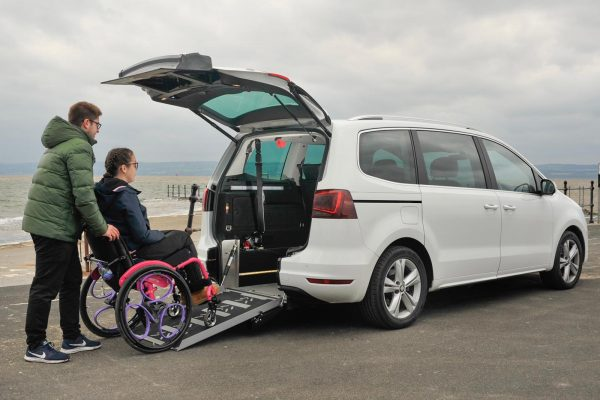 Lauren is sitting in a bright pink wheelchair that is being pushed up the access ramp of a white Seat Alhambra by her carer Felix.