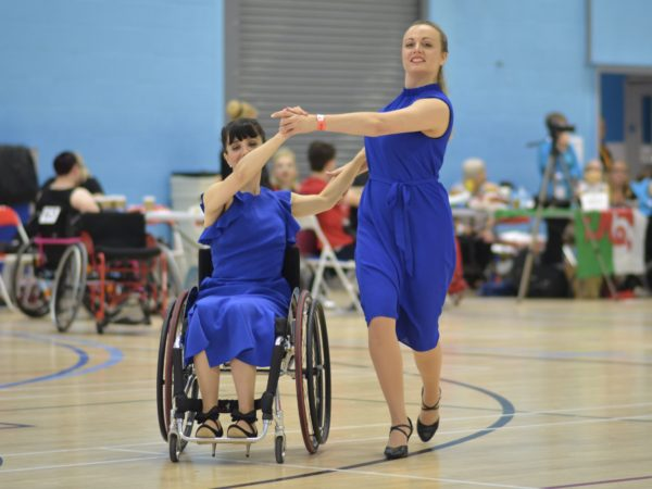 Two Para Dance members dancing together (one wheelchair user and one able-bodied). They are both wearing a royal blue dress.