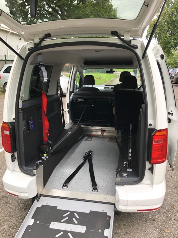 White Volkswagen Caddy Maxi with deployed wheelchair access ramp and two tie down brackets.