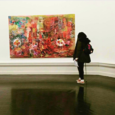Hannah is facing away from the camera, looking at a large, brightly coloured abstract art piece on a wall in a gallery. She is wearing black jeans, a dark green winter coat, and a galaxy backpack. She is using a mint green walking stick.