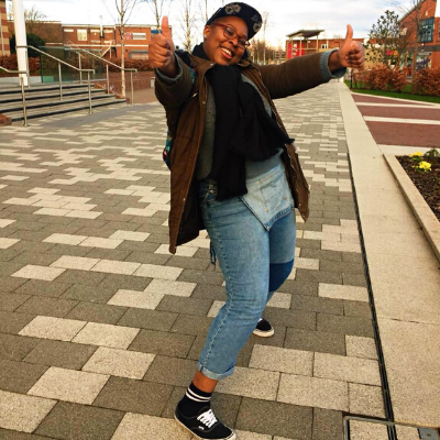 Hannah is in an outdoor setting, smiling, giving two thumbs up at the camera. She is wearing denim dungarees, a blue jumper, dark green winter coat, a black scarf, and a black snapback.