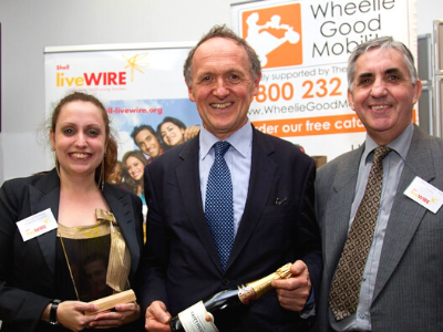 Charmaine Kemp and Bob Kemp standing either side of a man who is holding a bottle of champagne. They are in front of two banner stands, one for Wheelie Good Mobility, and Charmaine is holding an award.